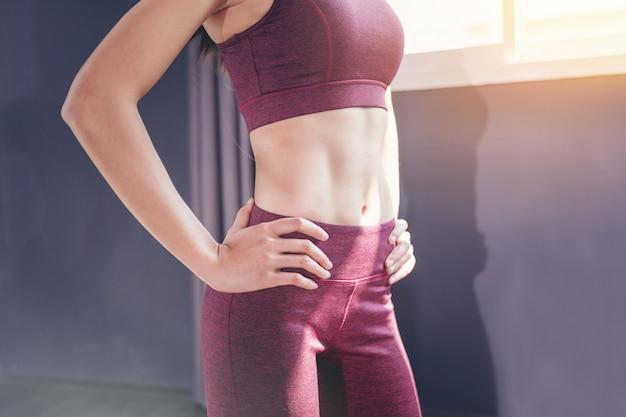 A posição apta do exercício da mulher mostra sua forma no gym da aptidão.