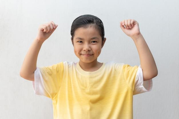 A posição asiática da menina faz o gesto do vencedor.