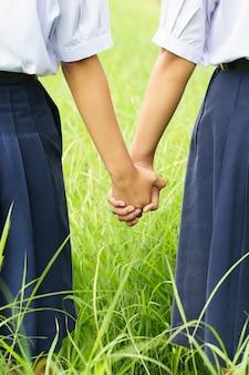A posse do estudante suas mãos no campo verde, conceito dos melhores amigos.