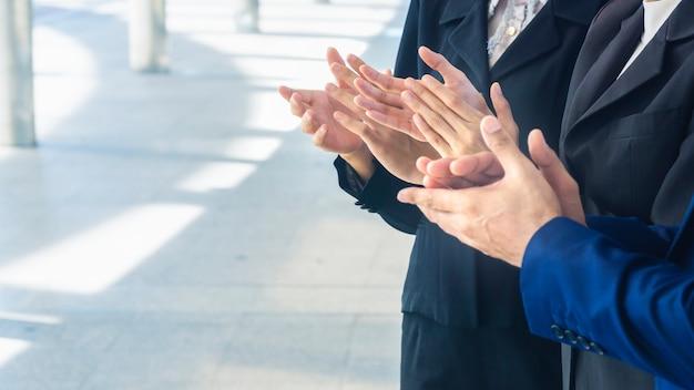 A postura batendo palmas de pessoas na suite de negócios.