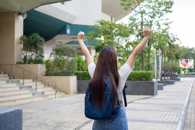 A postura relaxada da aluna asiática se sentiu muito feliz depois da escola durante o intervalo. carregando uma mochila, pronta para ir para casa.