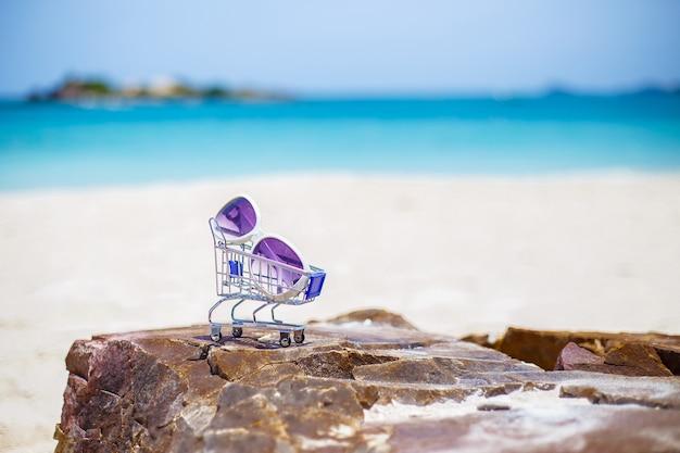 A praia com os óculos de sol na rocha, espaço da cópia para o texto.