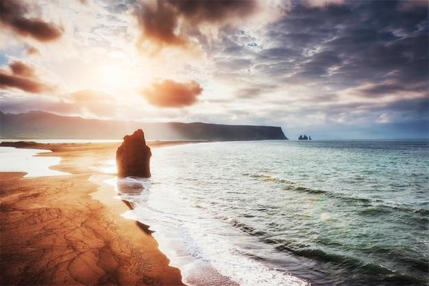 A praia de areia preta e as montanhas reynisfjara reynisfyal