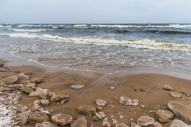 A praia de inverno do mar báltico tem neve e ondas fortes no mar