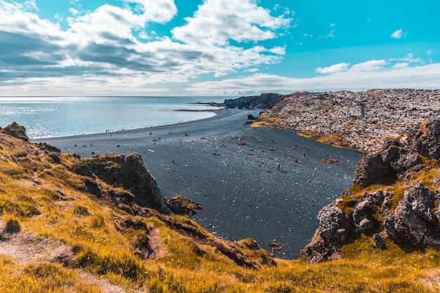 A praia de pedra negra gigante acima da costa de snaefellsnes. islândia