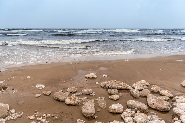 A praia fria de inverno do mar báltico tem neve e há ondas fortes no mar, em saulkrasti, na letônia