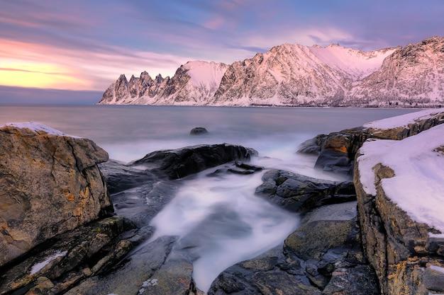 A praia rochosa e piscinas ao pôr do sol na ersfjord. ilha senja na região de troms, no norte da noruega. tiro de longa exposição