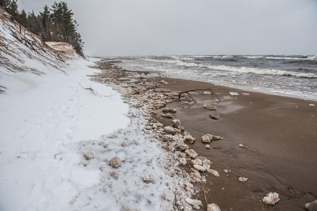 A praia selvagem do mar báltico tem neve no inverno e há grandes ondas no mar em saulkrasti, na letônia