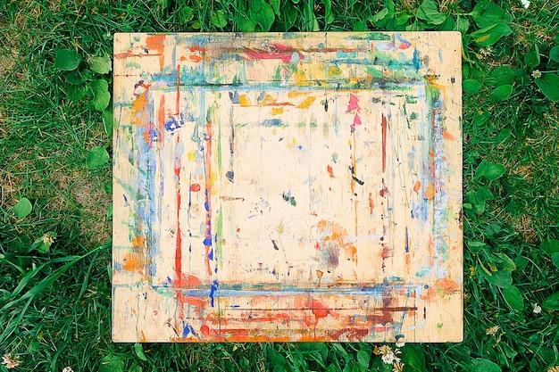 A prancha de madeira está manchada e salpicada de tinta brilhante, deitada na grama verde. a vista do topo. plano de fundo texturizado.