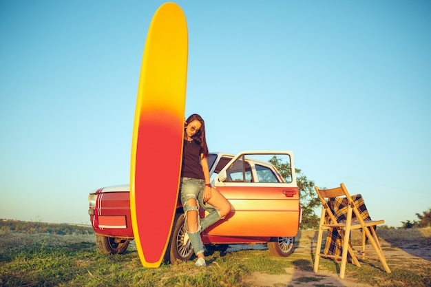 A prancha de surf, carro, mulher.
