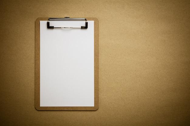 A prancheta de brown e o livro branco cobrem no fundo de papel reciclado marrom.