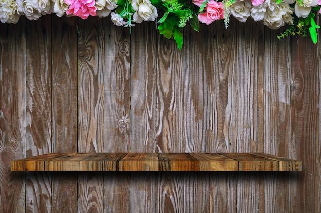 A prateleira de madeira fica nas pranchas de madeira velhas, com rosas decoradas em cima.
