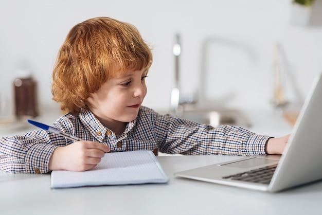 A preparação como arma principal. garoto inteligente e comprometido lendo um livro em seu laptop e fazendo anotações enquanto está sentado à mesa da cozinha