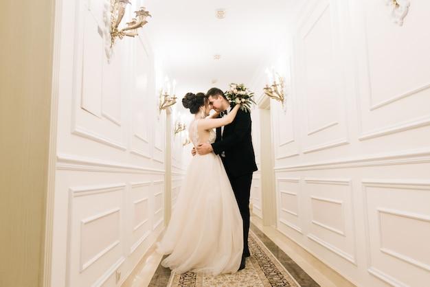 A primeira reunião da noiva e do noivo no brilhante corredor de um hotel de luxo. dia do casamento