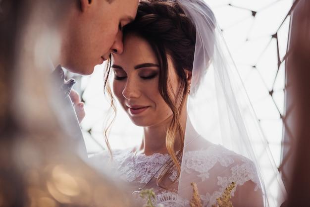 A primeira reunião. o noivo entra no quarto para a noiva com um buquê. eles se abraçam e se beijam. vestido de noiva rosa, terno cinza e buquê elegante. quarto no estilo de marrocos.
