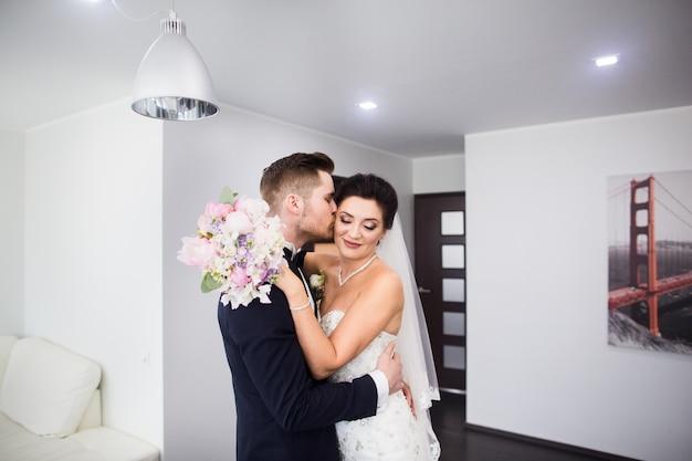 A primeira reunião. o noivo entra no quarto para a noiva com um buquê.