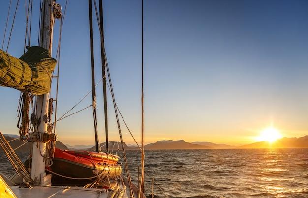A proa de um iate à vela, flutuando no mar para a costa contra o amanhecer.
