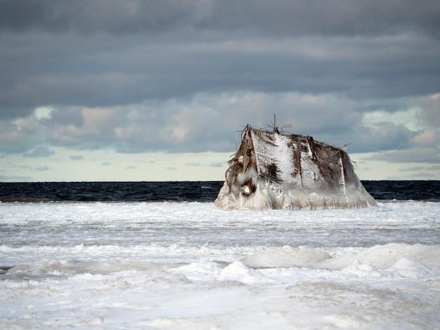 A proa do naufrágio está congelada no mar. tudo em volta de neve e nuvens no céu.