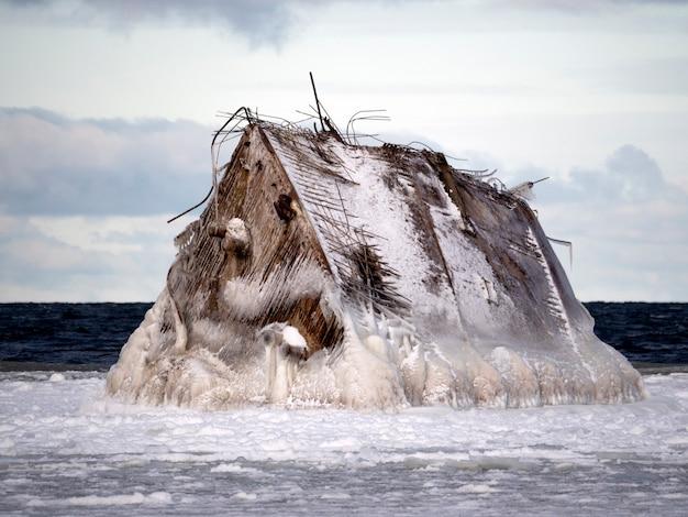 A proa do naufrágio está gelada em close-up do mar. tudo em volta de neve e nuvens no céu.