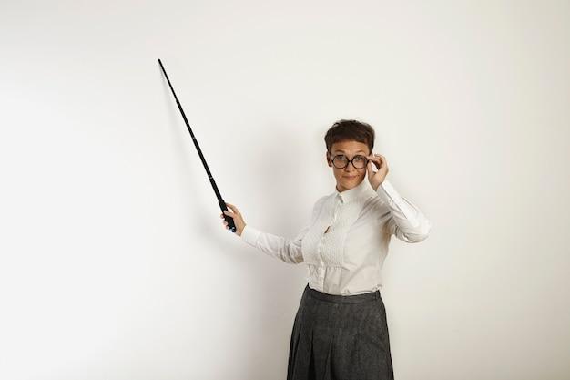 A professora branca de aparência conservadora aponta para um quadro branco em branco com um ponteiro telescópico preto e ajusta seus óculos redondos pretos