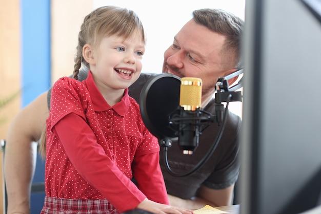 A professora com a garotinha está gravando uma música no estúdio, ensinando o conceito vocal para crianças