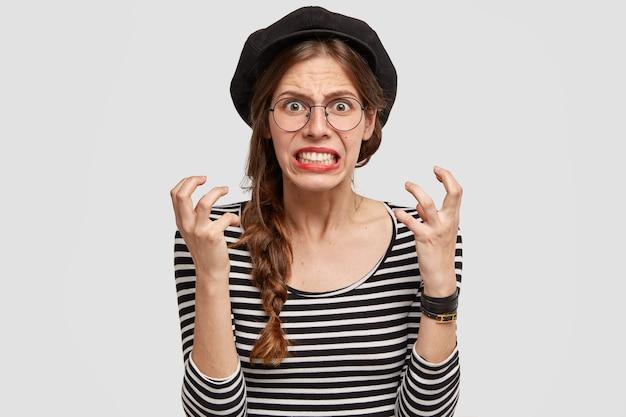 A professora de francês irritada cerra os dentes e gesticula com raiva, parece impaciente, tem expressão facial negativa, usa boina, posa sobre parede branca