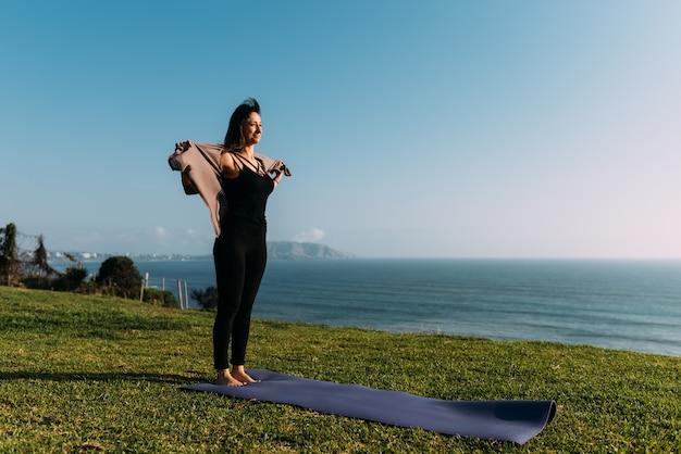 A professora de ioga se descobre fazendo ioga no tapete que está apoiado na grama em frente ao mar. copie o espaço