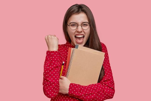 A professora positiva e feliz fecha o punho com uma expressão alegre, segura o bloco de notas em espiral, escreve notas no bloco de notas, vestido com uma camisa vermelha