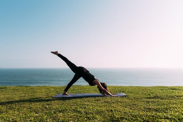 A professora pratica ioga no gramado em frente ao mar. copie o espaço