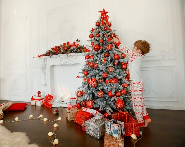 A própria criança decora a árvore de natal Foto Premium