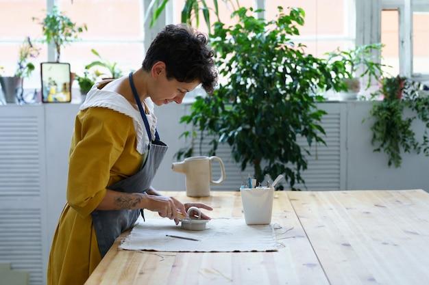 A proprietária de um estúdio de cerâmica, uma jovem ceramista, prepara utensílios de cozinha para uma aula de oficina no estúdio criativo
