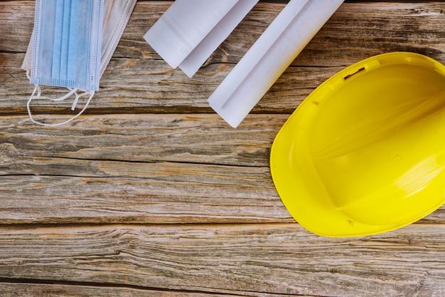 A proteção da máscara facial para prevenção de coronavírus está no construtor de projetos de arquitetos que trabalham nos planos de construção do escritório de engenharia no capacete amarelo do capacete de segurança