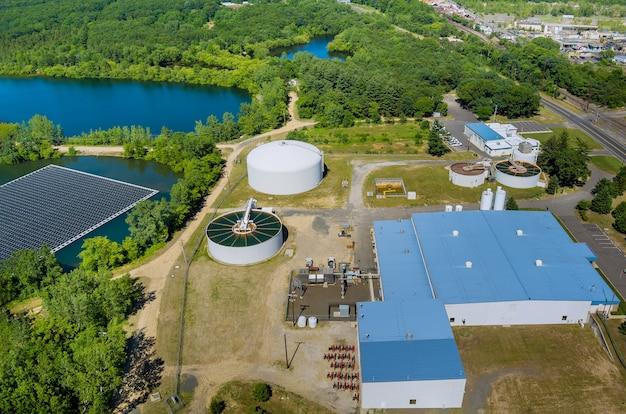 A purificação da água é o processo de remoção de produtos químicos indesejáveis da moderna estação de tratamento de águas residuais urbanas perto da plataforma flutuante de células de painéis solares no belo lago