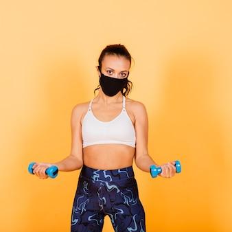 A quarentena não é um obstáculo. atleta de pele escura usando uma máscara médica, treinando com halteres. conceito de saúde, fitness e quarentena.
