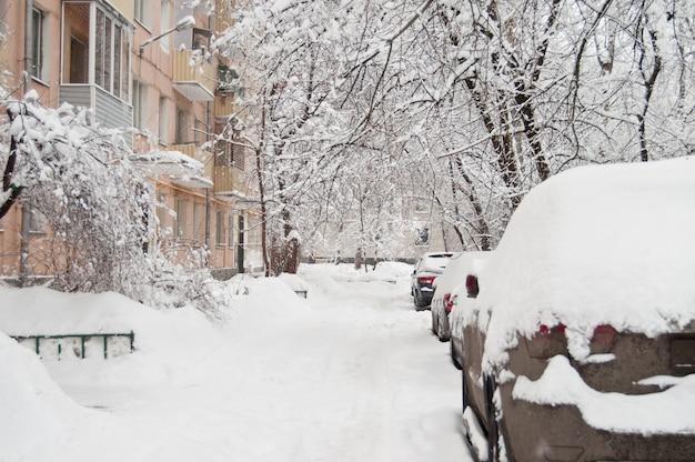 A queda de neve mais forte. carros cobertos de neve no quintal.