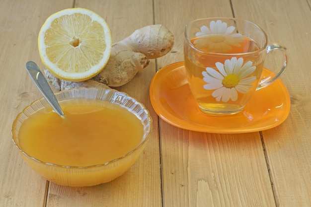 A raiz de gengibre e mel na mesa de madeira.