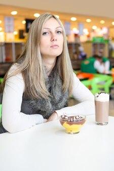 A rapariga a comer sobremesas doces no café