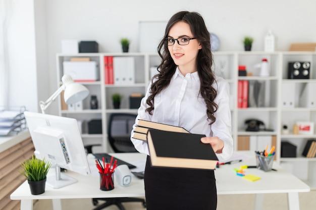A rapariga bonita está no escritório, prende uma pilha de livros em suas mãos e estica para a frente
