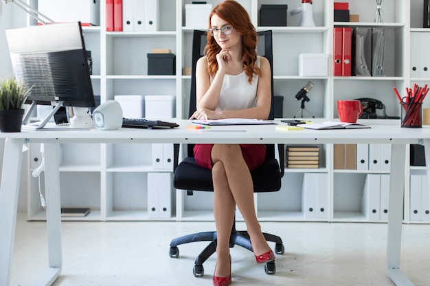 A rapariga bonita está sentando-se na mesa no escritório.