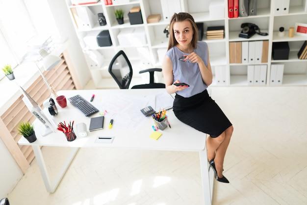 A rapariga bonita no escritório está sentando-se na mesa e está prendendo vidros e um telefone.