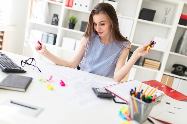A rapariga bonita no escritório senta-se em uma tabela e realiza-se em marcadores amarelos e cor-de-rosa das mãos.