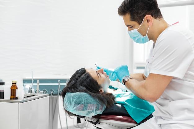 A rapariga bonito está sendo examinada pelo dentista