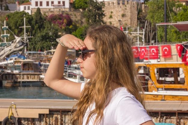 A rapariga com cabelo longo senta-se no cais na porta do iate e olha o mar azul