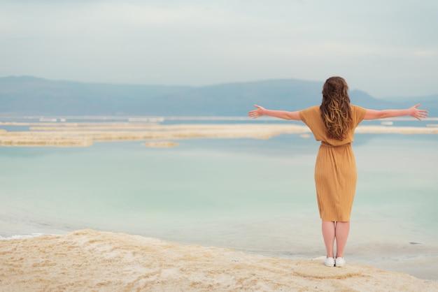 A rapariga com cabelo louro de brilho vai ao beira-mar
