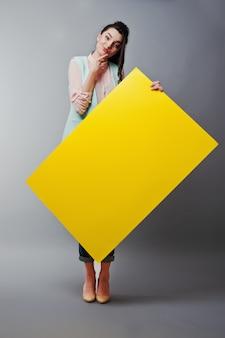 A rapariga com cara segura o papel em branco amarelo. jovem mulher mostrar cartão em branco. menina com retrato de cabelos longos, isolado no fundo cinza.