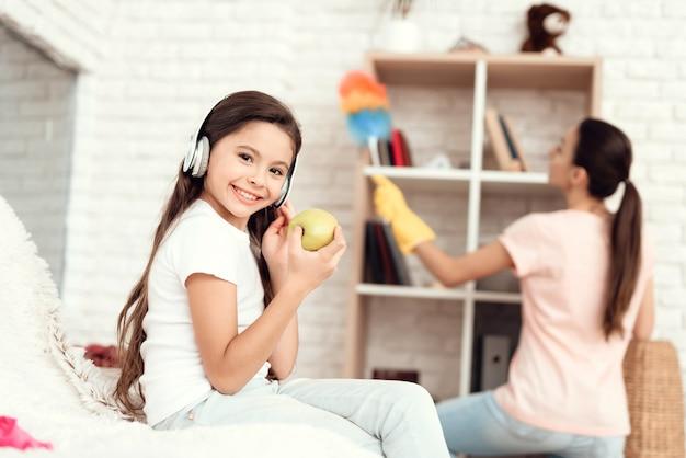 A rapariga come uma maçã e descansa quando sua mãe limpar