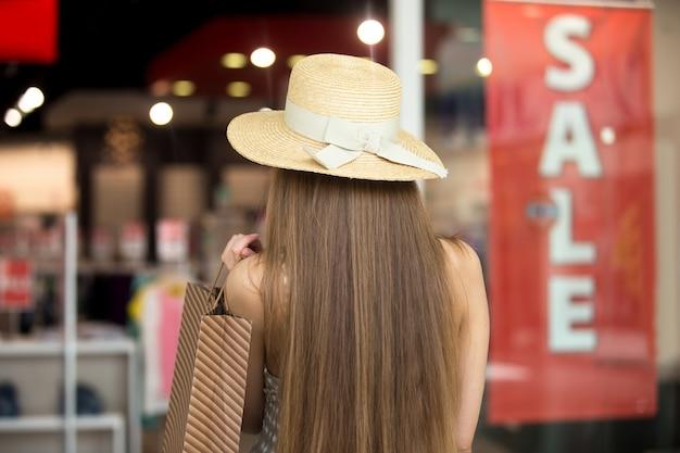 A rapariga de costas com um chapéu de palha
