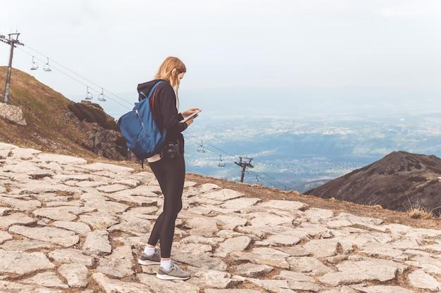 A rapariga em uma camisola preta e em leggings está nas montanhas e usa o telefone