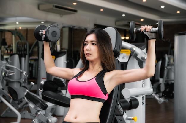 A rapariga está exercitando na aptidão.
