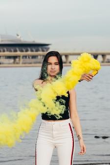 A rapariga feliz bonita no beira-mar prende uma luz acima das bombas de fumo coloridas.